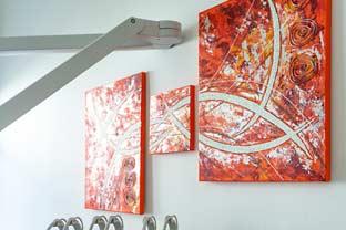 Eine Wand im Beandlungszimmers mit drei roten, abstrakten Gemläden ist zu sehen