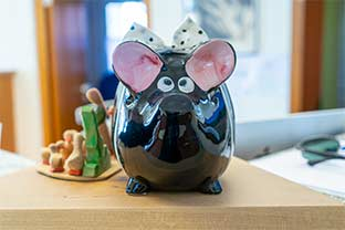 Trinkgeld-Spardose in form eines Schweinchens mit schielenden Augen, rosa Öhrchen und weißer Schleife steht auf dem Tresen, Hintergrund der Praxis ist verschwommen