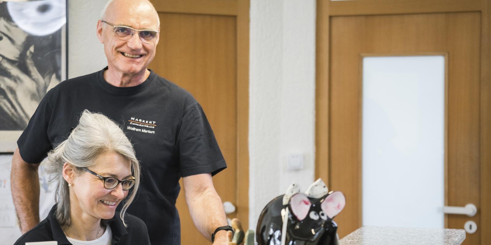Zahnarzt W. Markert und Zahnarzthelferin Frau Horn sind am Tresen der Praxis, beide sind Brillenträger, tragen dunkelblaue Shirts mit Praxislogo und lächeln