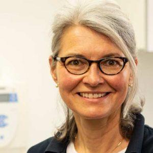 Zahnarzthelferin Claudia Horn lächelt frontal in die Kamera, sie trägt eine schwarze Brille und trägt ihr Haar locker im Nacken zusammengefasst