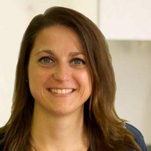 Dentalhygienikerin Tamara Zwillich ist zu sehen; sie trägt ihr braunes, glattes, langes Haar offen und lächelt frontal in die Kamera