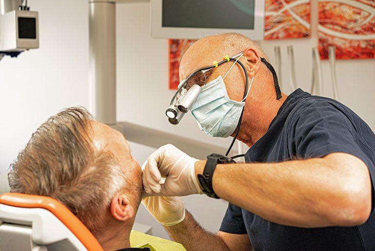 Zahnarzt W. Markert ist mit Mundschutz und Stirnlampe in Seitenansicht zu sehen, wie er den Mund eines Patienten inspiziert