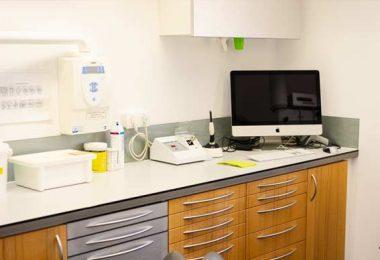 Deteailaufnahme im Behandlungszimmer des Sideboards auf dem ein PC, Desinfektionsmittel, Sterilisator und einige weitere Instrumente stehen