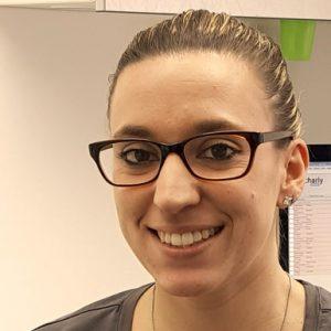 Lisa Dorsch, Zahnarzthelferin, dunkelhaarige Frau mit blonden Strähnen und Brille blickt lächelnd in die Kamera