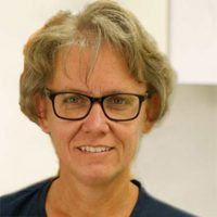 Zahnarzthelferin Petra Kunert trägt eine schwarze Brille und hat blonde halblange Haare und lächelt frontal in die Kamera