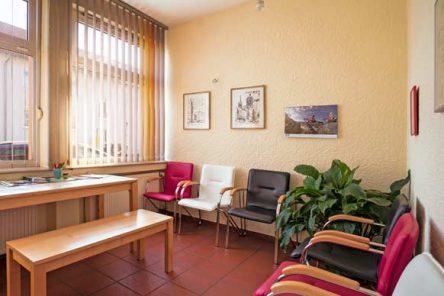 Einblick in das Wartezimmer mit bunten Stühlen, Bildern an der gelb gestrichenen Wand und einem Rechteckigen Tisch mit einer Sitzbank davor